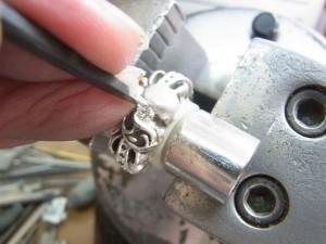 平タガネで銀の部分を少しづつ曲げていきます。