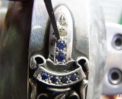 剣の部分の石留め中です。タガネで銀を彫って石を固定しています。