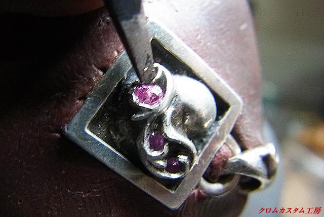 タガネで、銀の部分を叩いてサファイヤを固定します。
